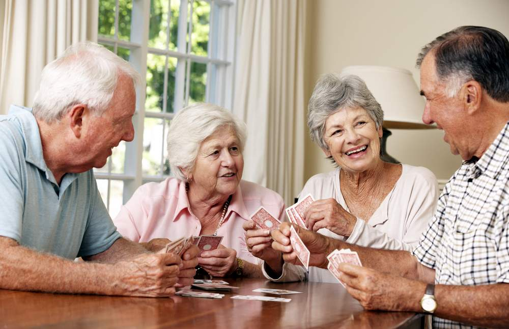 group of seniors playing games and doing fun activities at adult day care having fun.