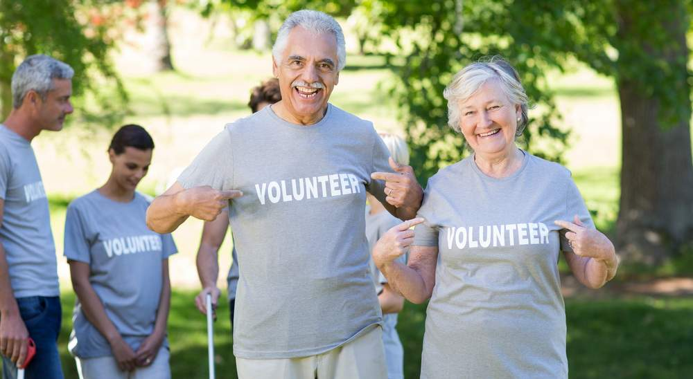 Happy volunteer seniors couple smiling at the camera on a sunny day