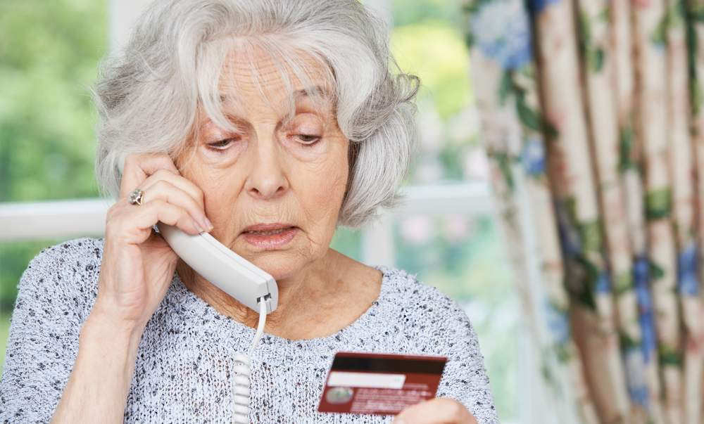 Senior Woman Giving Credit Card Details On The Phone wants to avoid scams targeting seniors